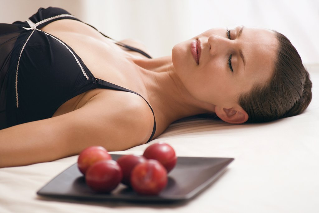 Young woman wearing neglige, relaxing on bed alongside tray with plums : Stock Photo