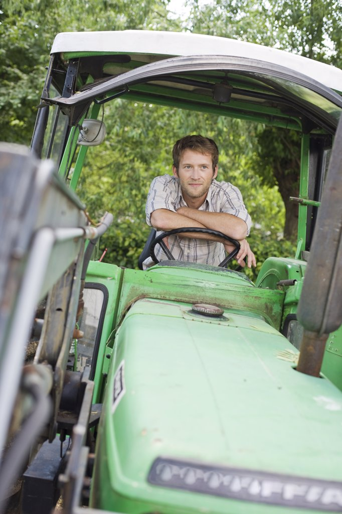 Farmer sitting in tractor : Stock Photo