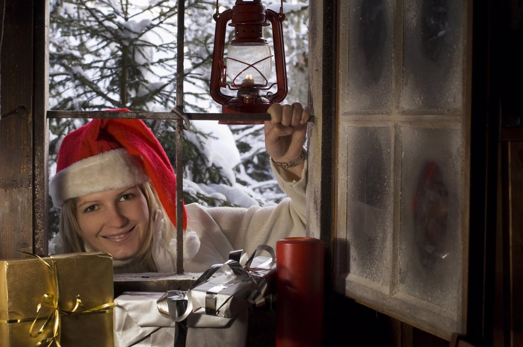 Austria, Salzburger Land, Woman with Santa's hat looking through window, Christmas parcels in foreground : Stock Photo