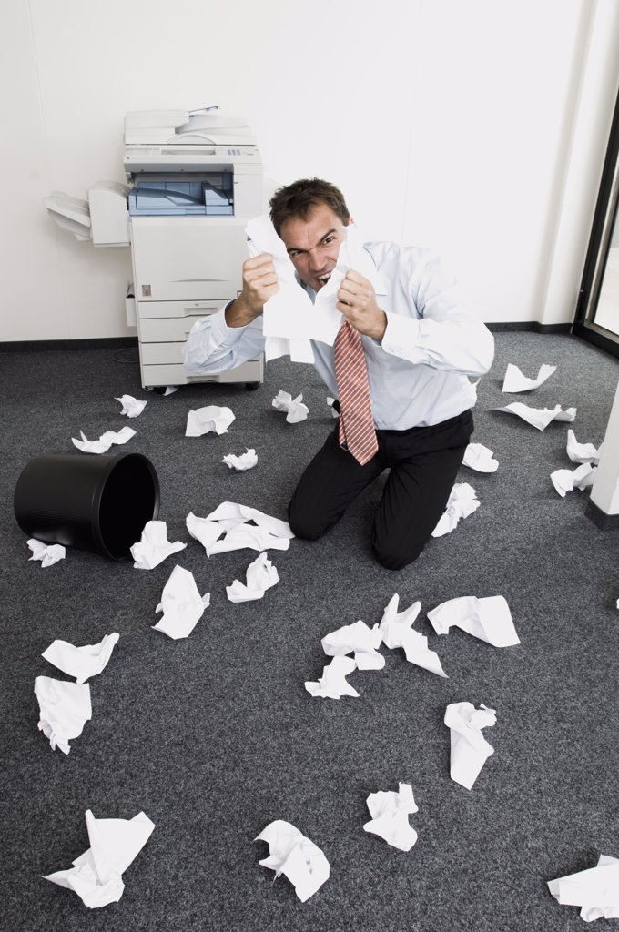 Stock Photo: 1815R-45986 Businessman kneeling in despair, tearing sheets of paper