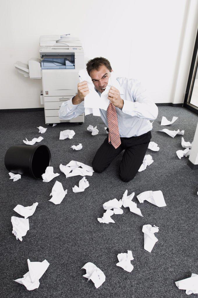 Businessman kneeling in despair, tearing sheets of paper : Stock Photo