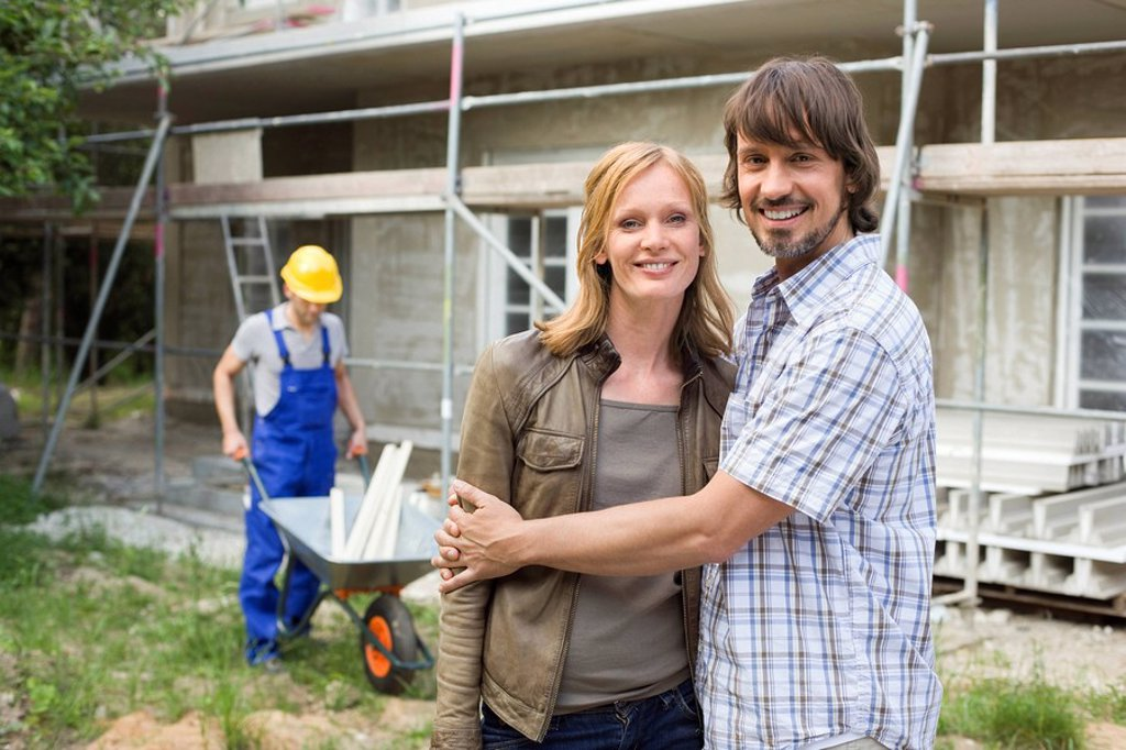 Young couple at site embracing, construction worker in background : Stock Photo