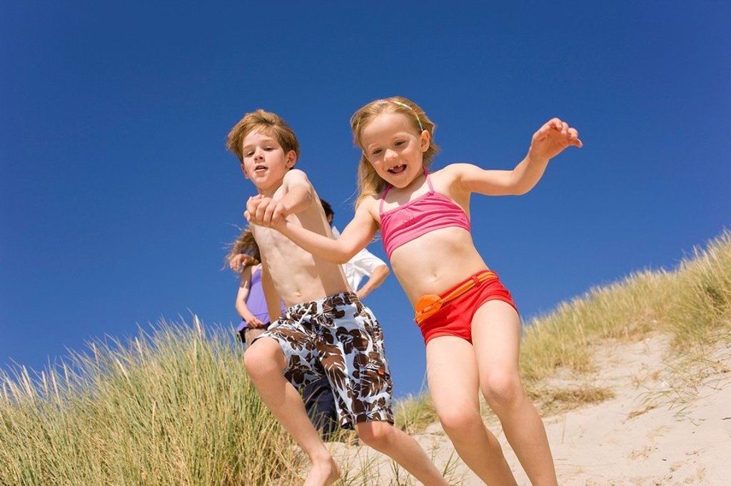 Stock Photo: 1815R-46611 Germany, Baltic sea, Boy 8_9 and girl 6_7 jumping down beach dune