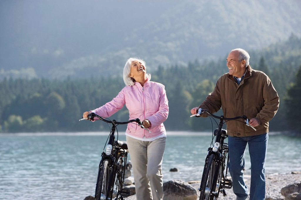 Stock Photo: 1815R-48900 Germany, Bavaria, Walchensee, Senior couple pushing bikes across lakeshore