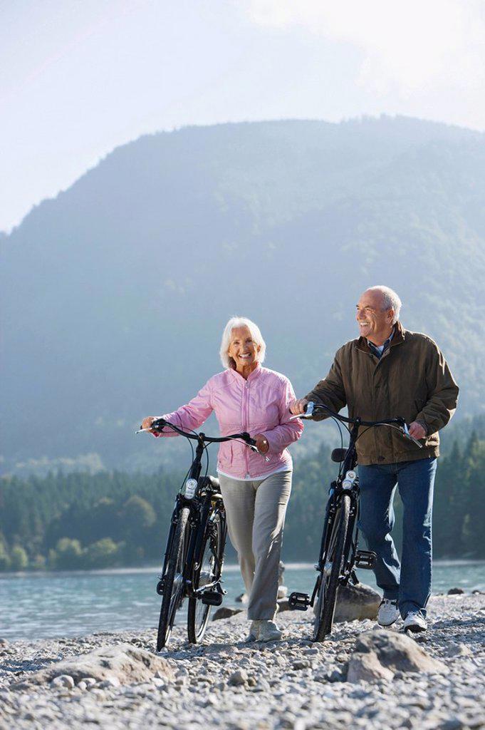 Stock Photo: 1815R-48902 Germany, Bavaria, Walchensee, Senior couple pushing bikes across lakeshore