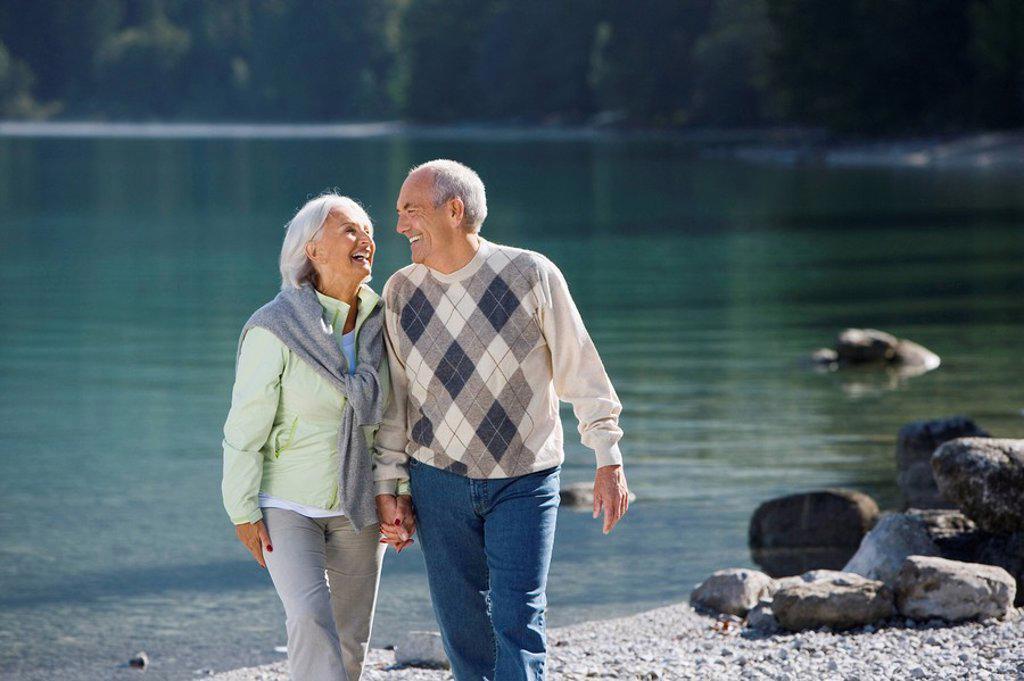 Germany, Bavaria, Walchensee, Senior couple walking across lakeshore : Stock Photo