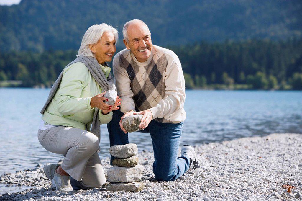 Germany, Bavaria, Walchensee, Senior couple piling up stones : Stock Photo