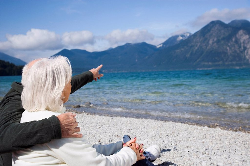 Germany, Bavaria, Walchensee, Senior couple relaxing on lakeshore, rear view : Stock Photo
