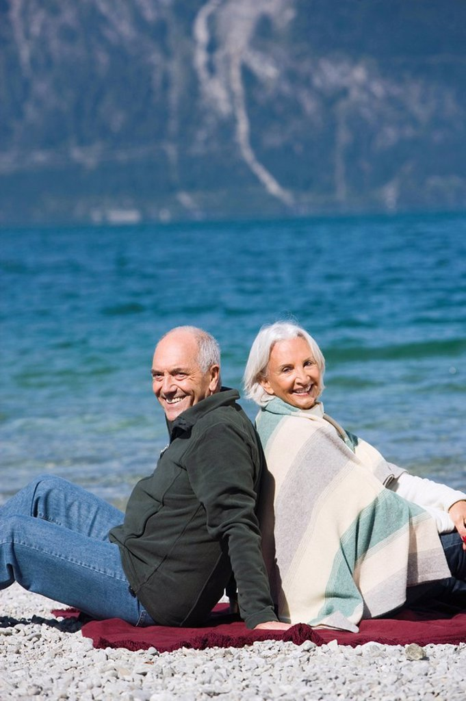 Germany, Bavaria, Senior couple relaxing on lakeshore, sitting back to back : Stock Photo