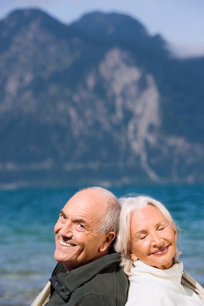 Germany, Bavaria, Senior couple relaxing on lakeshore, sitting back to back, smiling, portrait : Stock Photo