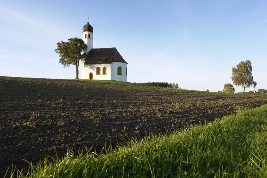 Germany, Bavaria, chapel with onion spire on a bank and fields : Stock Photo