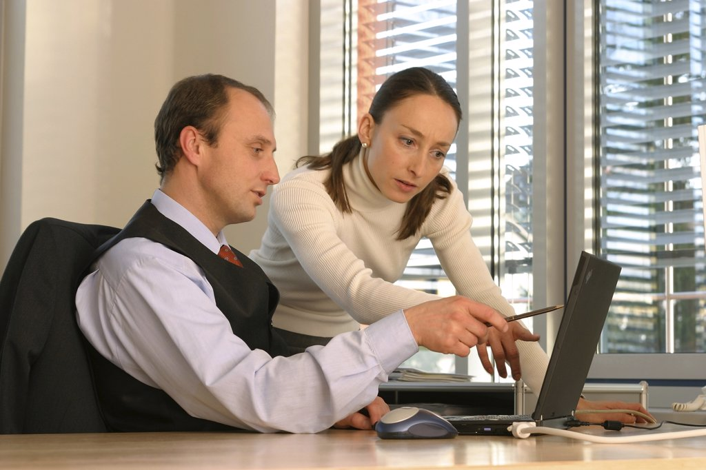 Stock Photo: 1815R-5113 Man and woman in office, working on laptop
