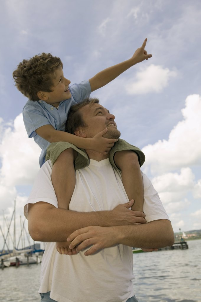 Stock Photo: 1815R-5139 Father carrying boy (6-7) on shoulders, smiling, low angle view