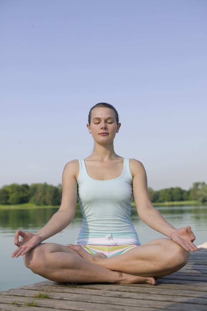 Stock Photo: 1815R-5167 Woman (20-25) exercising yoga on jetty