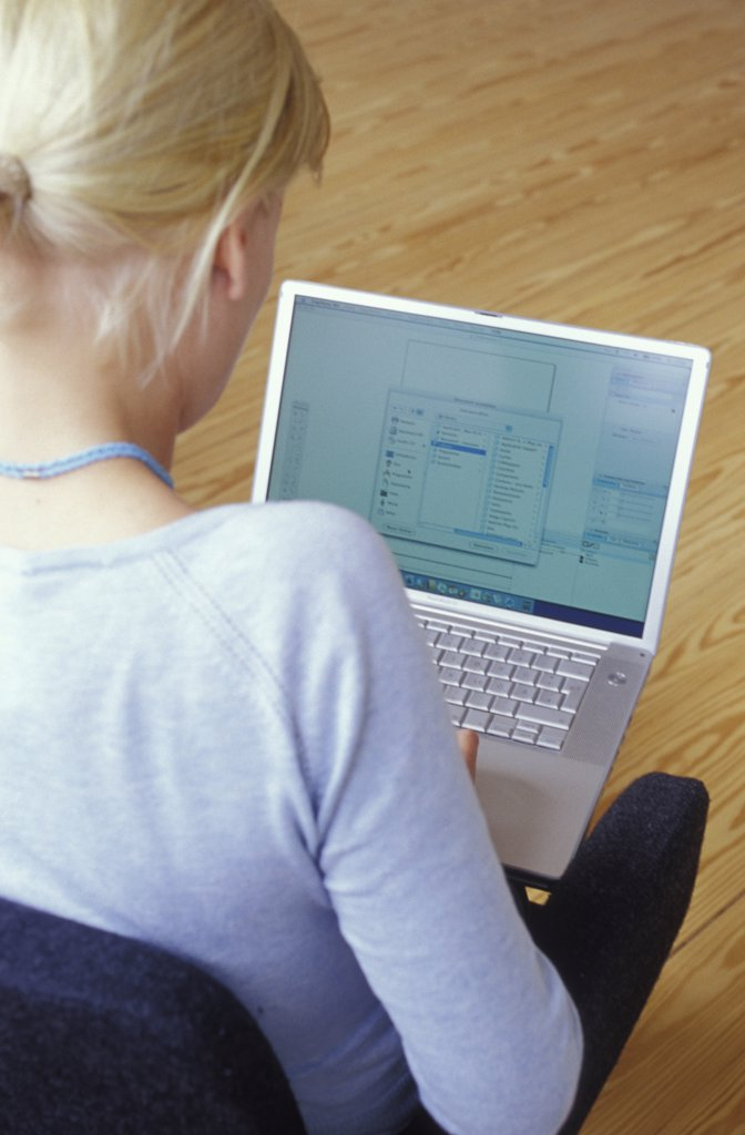 Girl (14-16) using laptop, rear view : Stock Photo