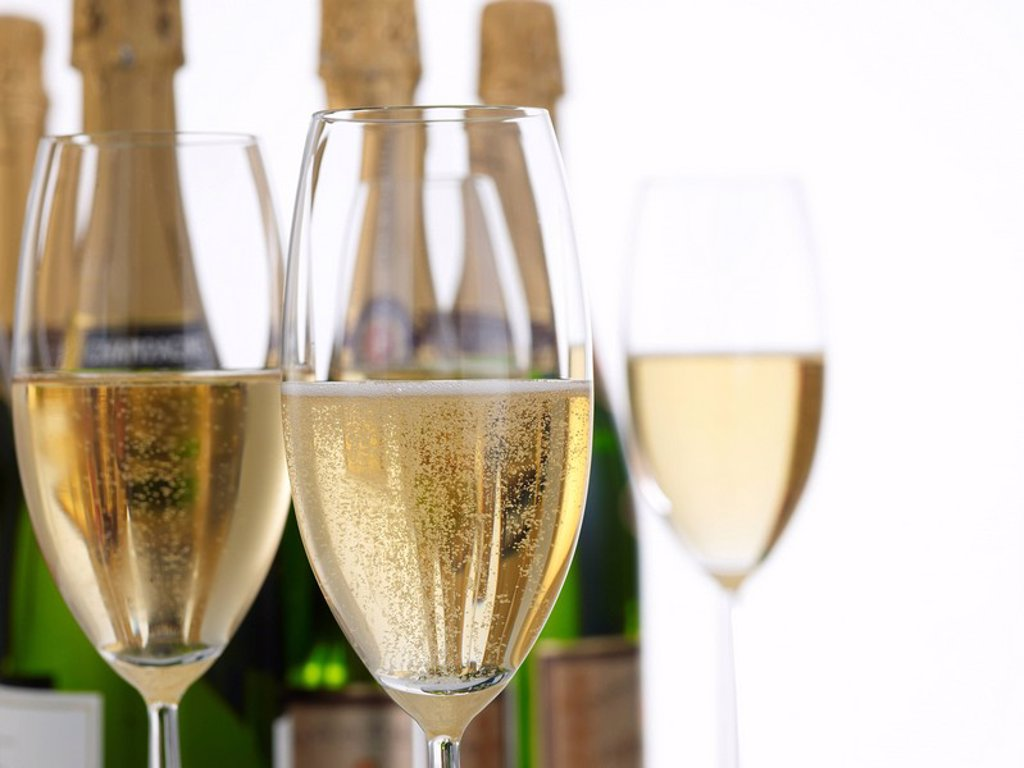 Champagne bottles and Champagne Glasses in foreground, close_up : Stock Photo
