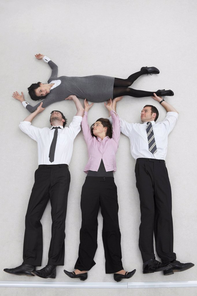 Four business people, businessmen and businesswoman lifting colleague, portrait, elevated view : Stock Photo