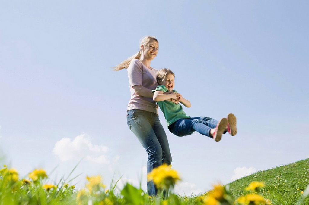 Stock Photo: 1815R-54220 Germany, Bavaria, Munich, Mother swinging daughter 6_7 on meadow, fooling about