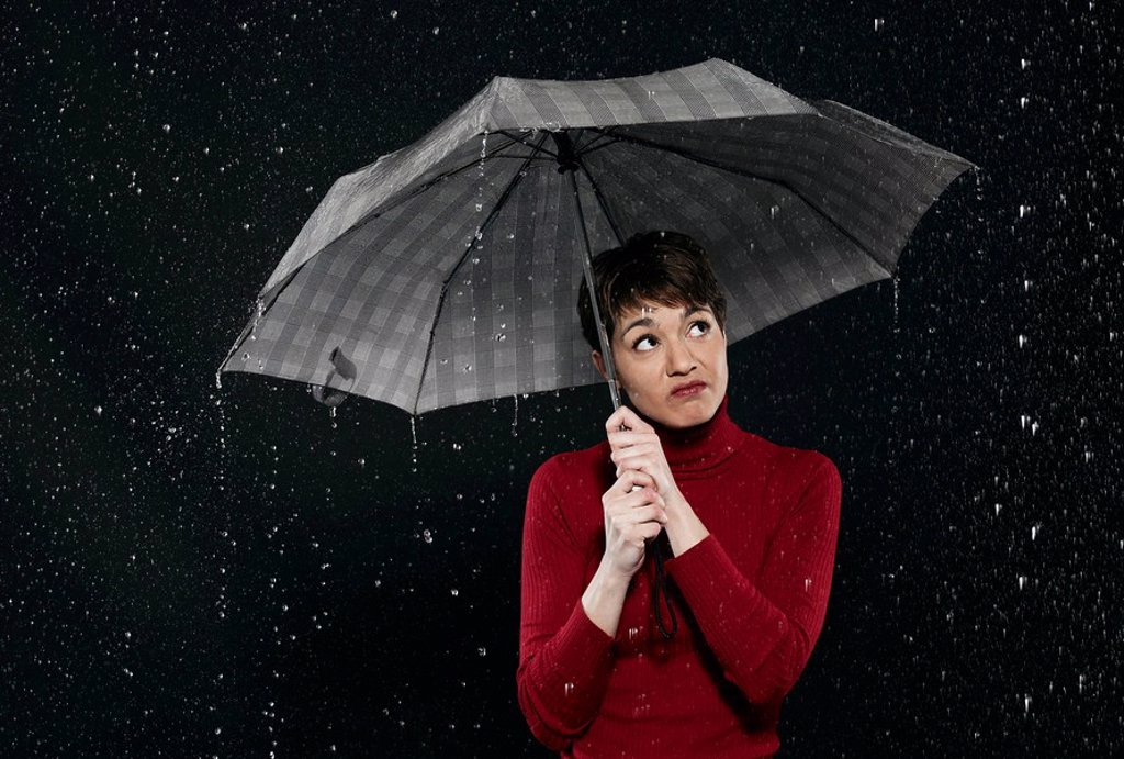 Woman standing in rain, holding umbrella. : Stock Photo