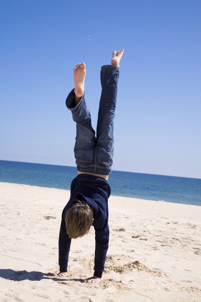 Portugal, Algarve, boy (8-11) doing handstand on beach, rear view : Stock Photo
