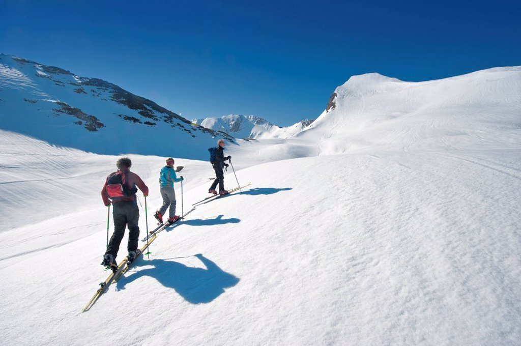 Austria, Salzburger Land, Altenmarkt, Zauchensee, Three persons cross country skiing in mountains, rear view : Stock Photo