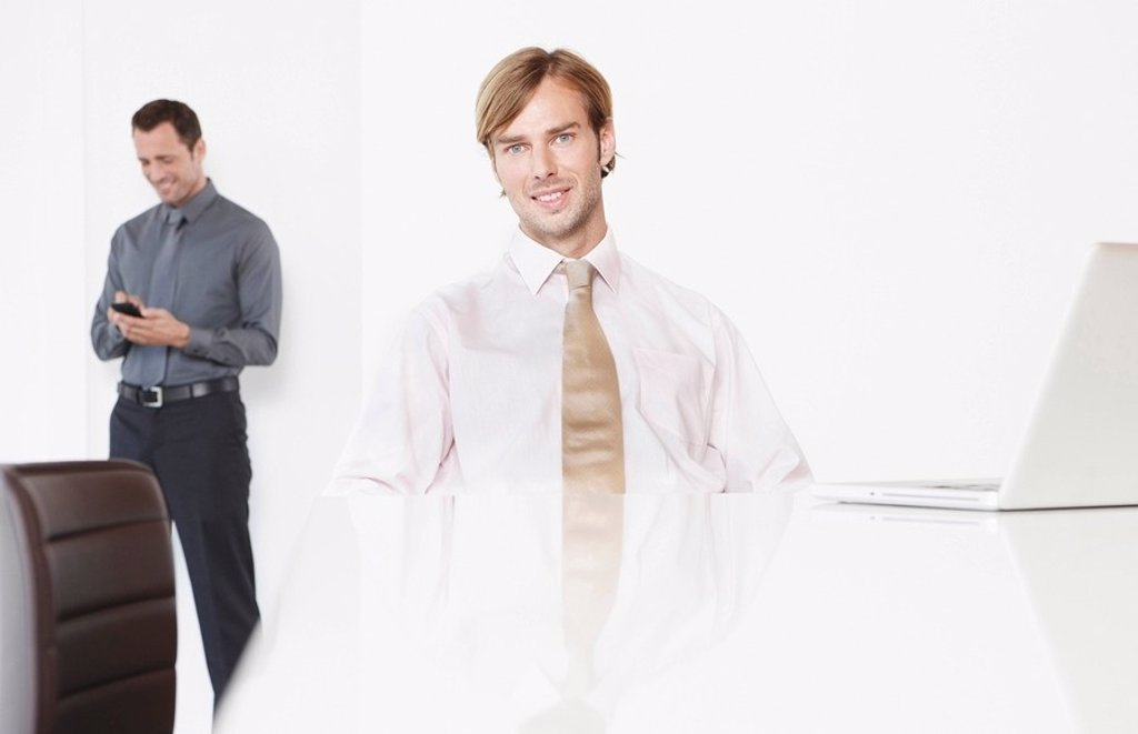 Stock Photo: 1815R-56694 Germany, Cologne, Two businessmen in conference room, laptop on desk