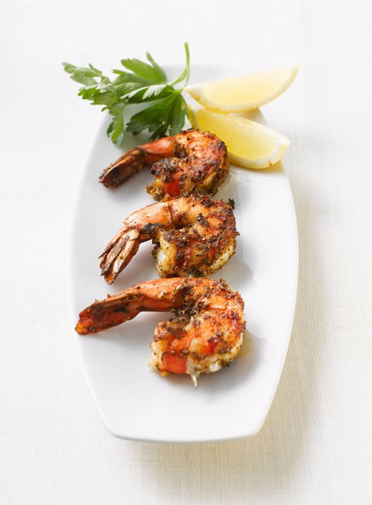 Grilled shrimps, parsley and lemon slices on platter, elevated view : Stock Photo