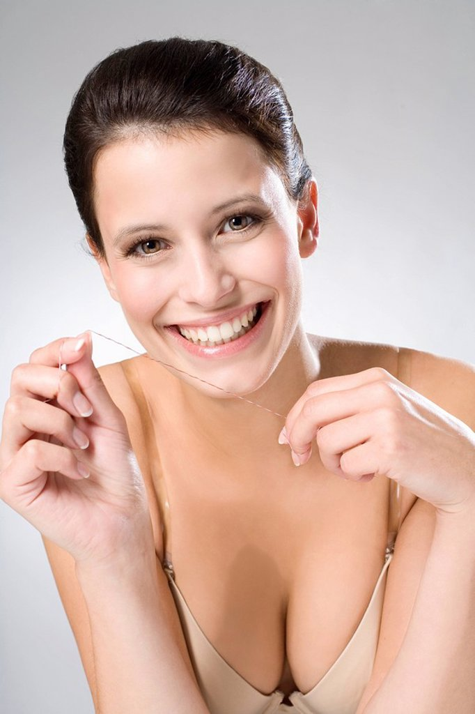 Stock Photo: 1815R-57803 Young woman flossing her teeth, close up