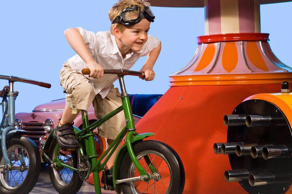 Germany, Landshut, little boy 4_5 riding carousel bike, smiling : Stock Photo