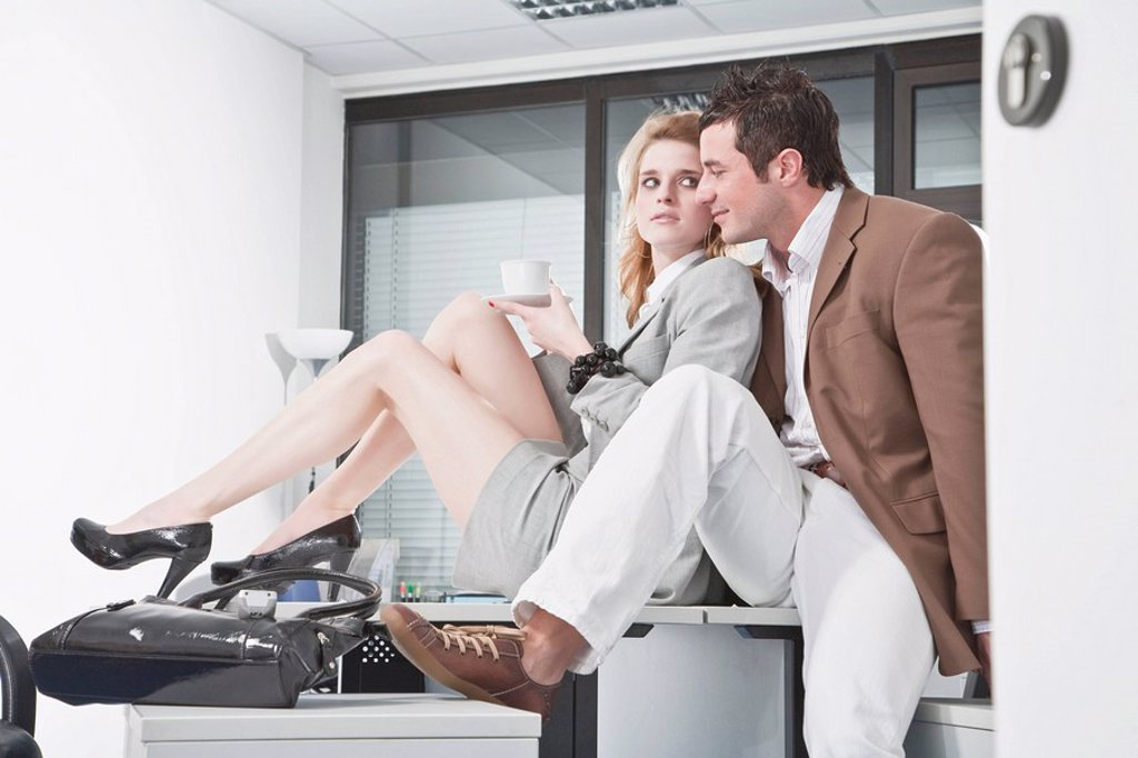 Germany, Business people in office, sitting on desk, flirting : Stock Photo