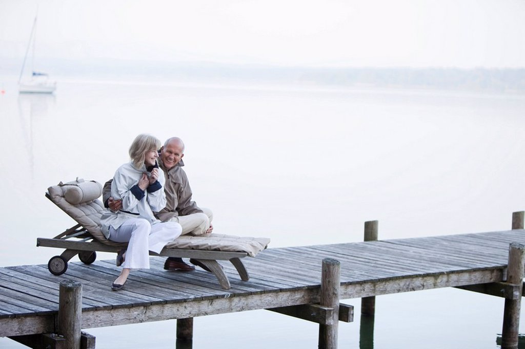 Germany, Bavaria, Starnberger See, Senior couple sitting on sunlounger on jetty : Stock Photo