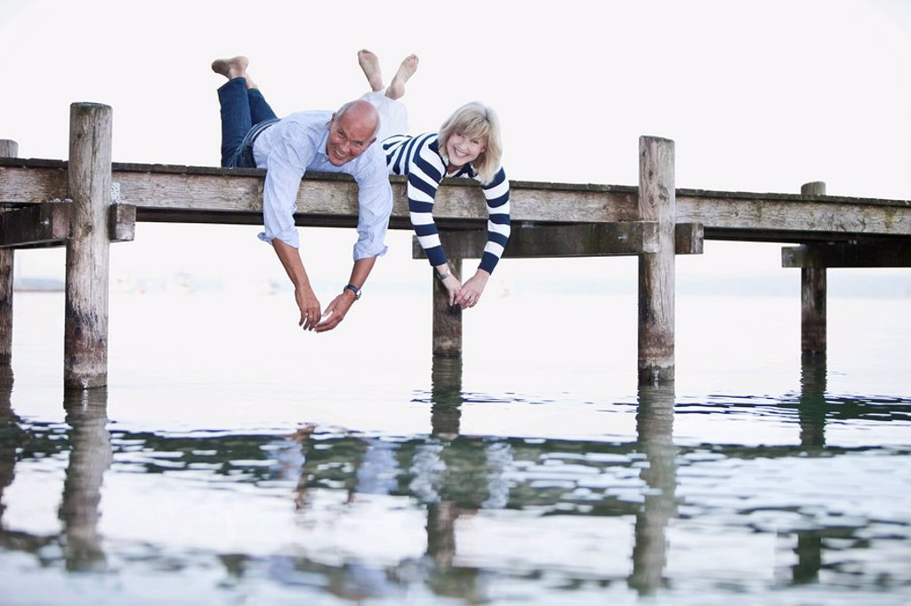 Germany, Bavaria, Starnberger See, Senior couple lying on jetty, smiling, portrait : Stock Photo