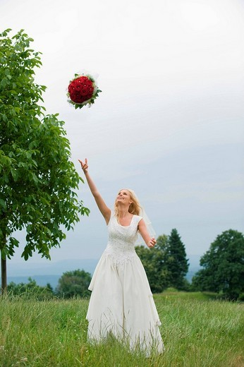 Stock Photo: 1815R-58865 Bride throwing up bouquet, smiling.