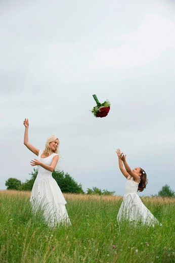 Stock Photo: 1815R-58869 Bride and flower girl 4_5 playing with bouquet on meadow