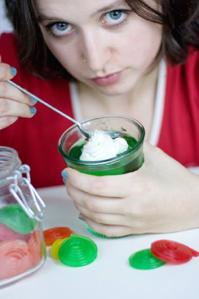 Young woman eating green jelly : Stock Photo
