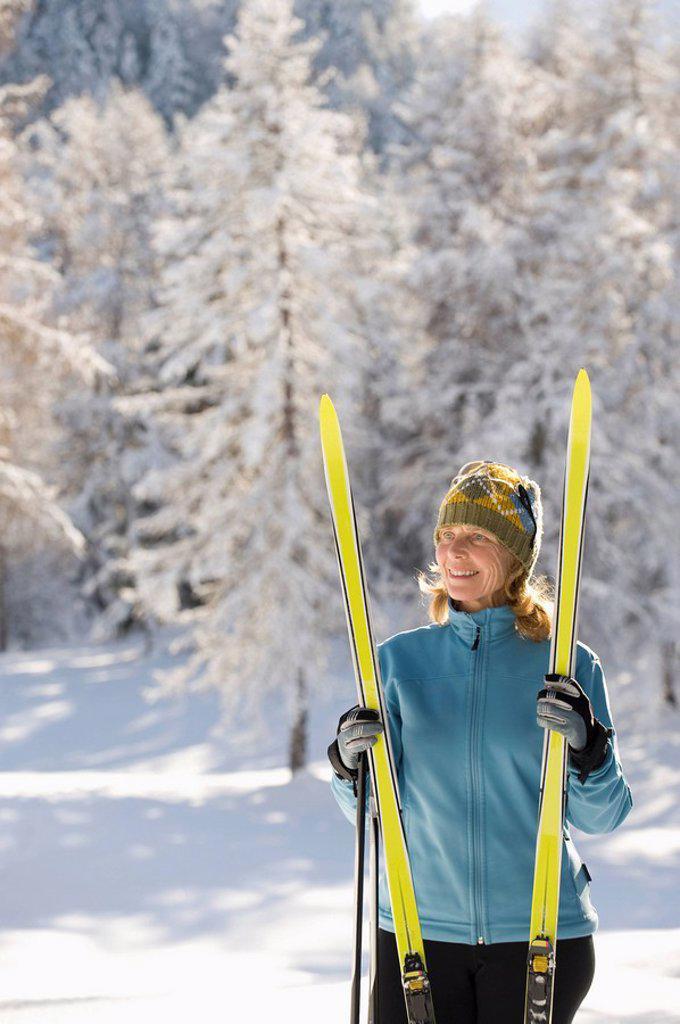 Austria,Tyrol, Seefeld, Wildmoosalm, Woman holding cross_country skis : Stock Photo