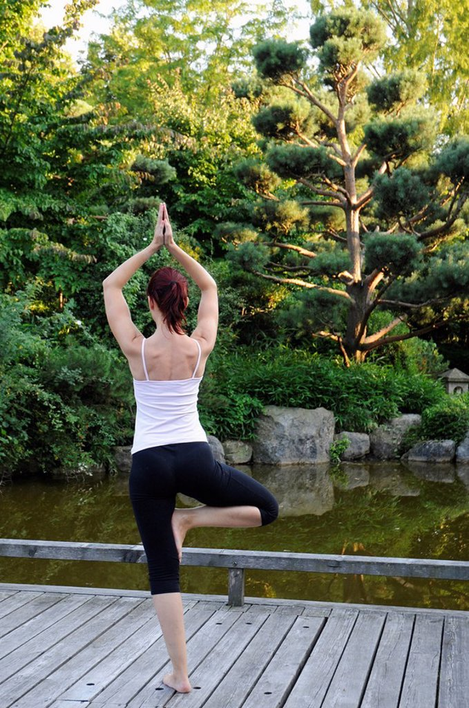 Stock Photo: 1815R-59249 Germany, Bavaria, Munich, Young woman exercising yoga, rear view