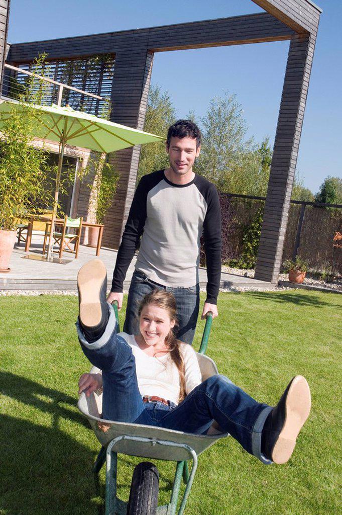 Stock Photo: 1815R-59325 Young man pushing woman in wheelbarrow