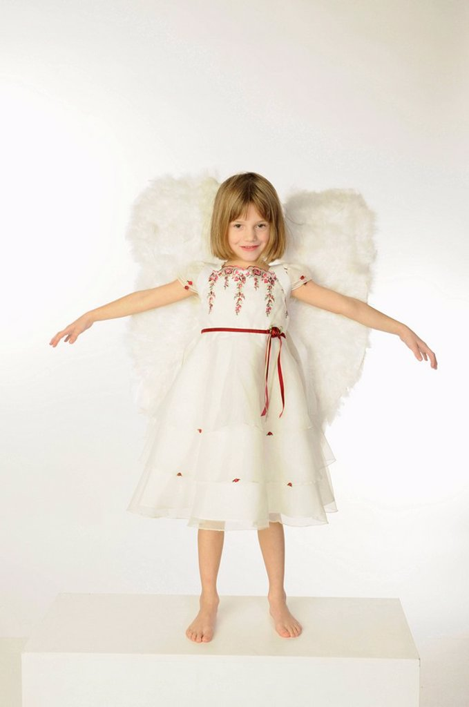 Little girl 6_7 wearing angel wings, arms out : Stock Photo
