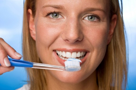 Young woman holding tooth brush, smiling, portrait : Stock Photo