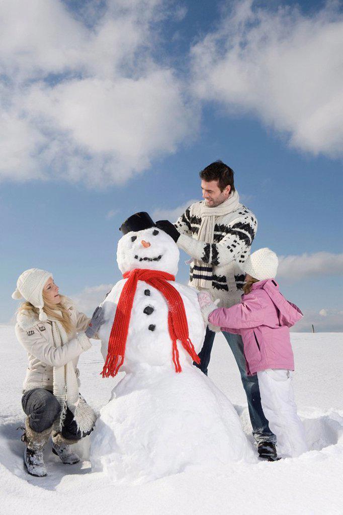Stock Photo: 1815R-60120 Germany, Bavaria, Munich, Family making a snowman, portrait