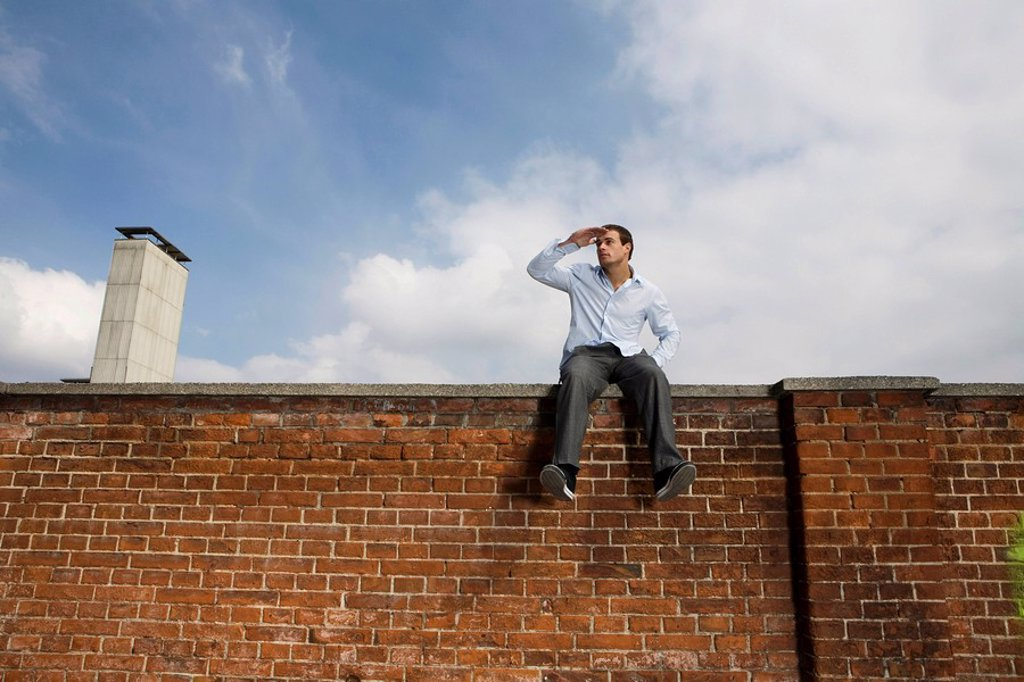 Stock Photo: 1815R-60140 Germany, Bavaria, Munich, Young man sitting on top of brick wall