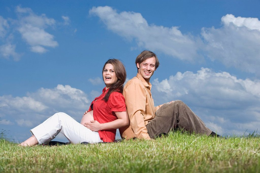 Couple sitting back to back in meadow, smiling, portrait : Stock Photo