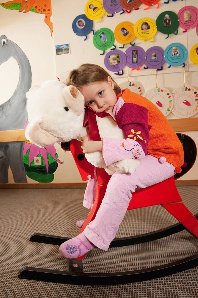 Germany, Girl 3_4 sitting on rocking horse, holding teddy, portrait : Stock Photo
