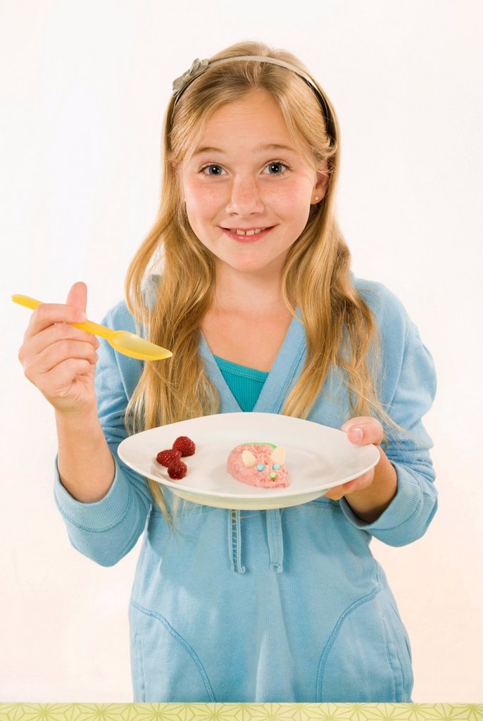 Girl 8_9 holding plate with food, portrait, close_up : Stock Photo