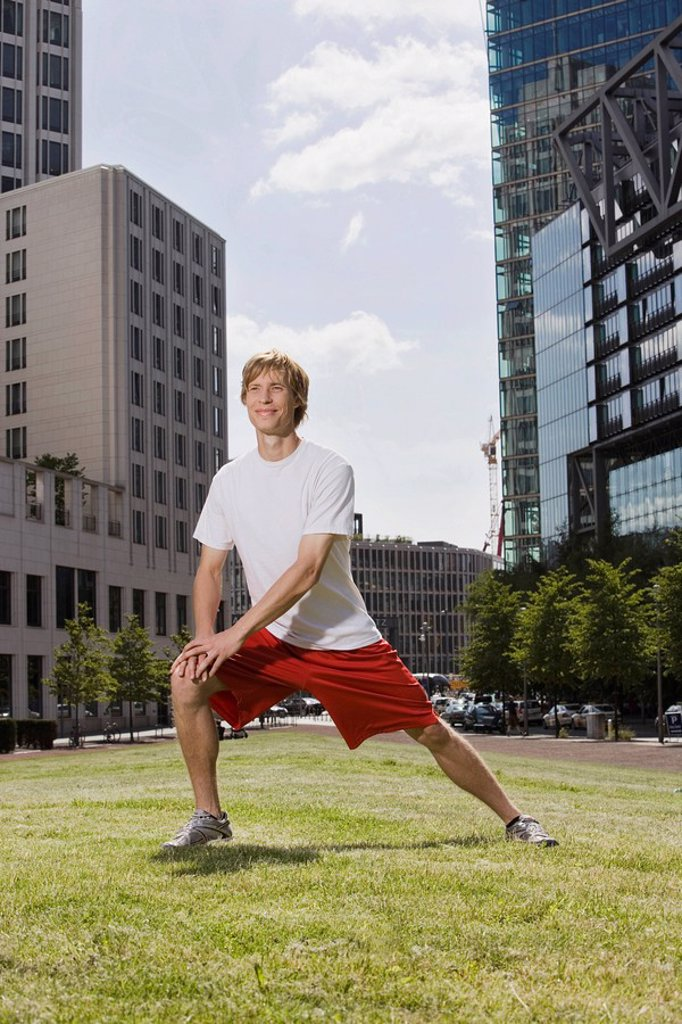 Germany, Berlin, Young man stretching on lawn : Stock Photo