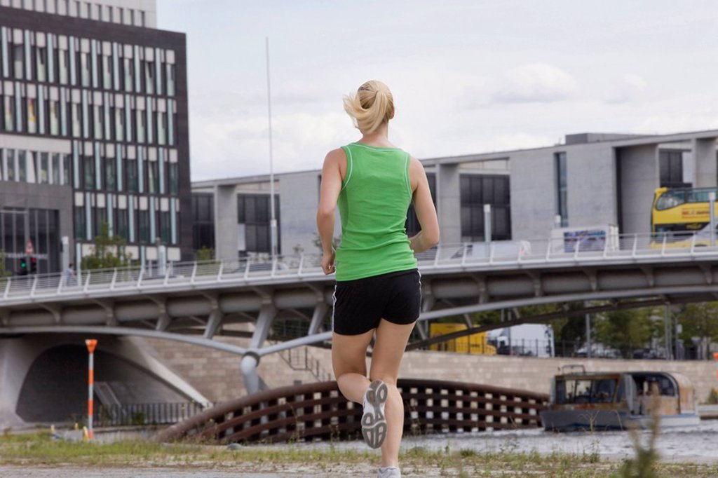 Germany, Berlin, Young woman jogging, rear view : Stock Photo