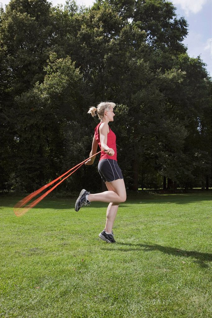 Germany, Berlin, Young woman jumping rope in park : Stock Photo