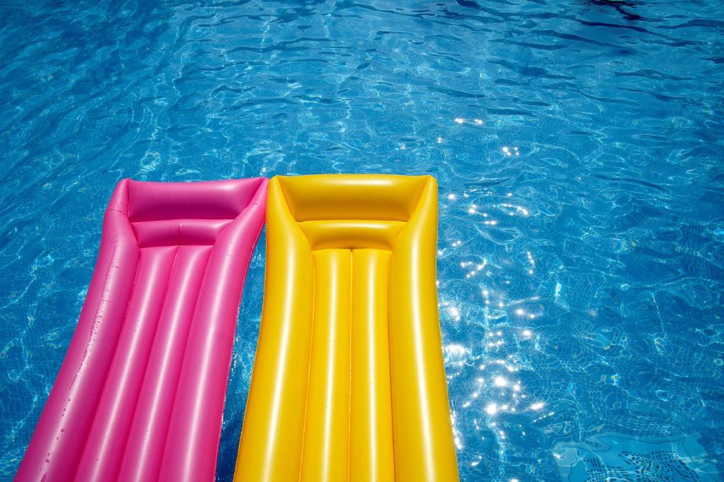 Two airbeds floating in pool, elevated view : Stock Photo