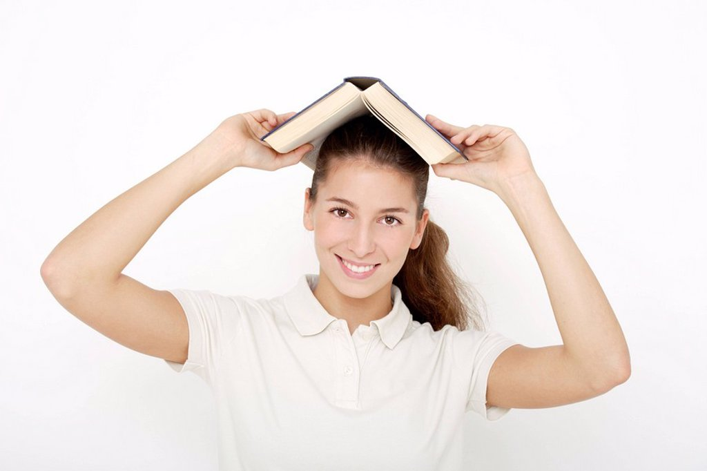 Stock Photo: 1815R-61637 Young woman 16_17 holding book over head